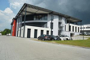 Der Parkplatz vor dem extravaganten Office Trendpark Süd in Neckarsulm wurde ganz bewusst mit schlichten grauen Betonpflastersteinen befestigt.