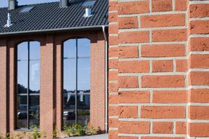 Die Vormauer für beide Gebäude ist im Wilden Verband errichtet worden. Der Terca-Vormauerziegel HKS Rot von Wienerberger und die kontrastierend helle Verfugung sorgen für die Anmutung von Industriearchitektur. Bauelemente wie Fenster und Türen unterstützen in Farb- und Formgebung den Lofteindruck.