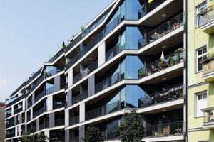 Ein skulpturaler Bau mit großen, teils schräggestellten Glasfassaden reflektiert im Berliner Samariterviertel Himmel und Nachbarschaft in verschiedenen Farben.