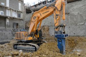 Der Hyundai R1200-9 auf einem riesigen Abbruchgebiet in Luxemburg. Der Gigant mit 567 kW bricht Stahlbetonfundamente mit einem 7-Tonnen-Hydraulikhammer auf, um Platz für ein Geschäftsviertel zu schaffen.