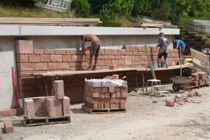 Klosterreichenbach, L 409: Verblendung der Stützmauer innerorts in herkömmlicher Bauweise. Betonieren und Verblenden mit Naturstein sind Arbeitsschritte, die nacheinander erfolgen. Das mehrfache Anliefern der Materialien und Bereitstellen des Personals verursacht einen zusätzlichen Aufwand schon bei der Planung des Bauablaufs.