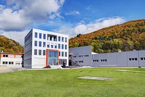 """Das Büro- und Verwaltungsgebäude """"Kubus AMF"""" setzt mit seiner klaren Formensprache einen spannenden Akzent im Ensemble der Werksgebäude von Knauf AMF in Grafenau."""