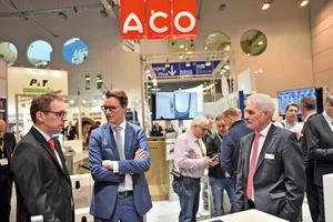 Auch NRW-Verkehrsminister Hendrik Wüst (mi.), hier im Gespräch mit Bernd Bathke (re.) ließ es sich nicht nehmen, sich auf dem Aco Messestand über aktuelle Produktentwicklungen des Marktführers im Bereich Entwässerungstechnik zu informieren.