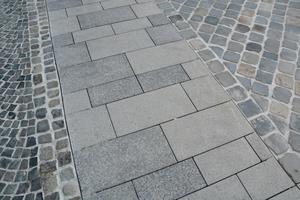Randausbildung entlang der Fassaden mit zweireihigem Natursteinband als taktiles Element sowie der angrenzenden Aufstellfläche aus gesägten Natursteinen.