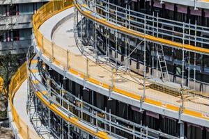 Drei Geschosse legen sich ringförmig und nach oben abgetreppt um den Kuppelbau. Das Peri Up Fassadengerüste und der Prokit-Seitenschutz sorgten für hohe Sicherheit während der Baumaßnahme.