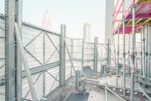 Sicheres Arbeiten hinter einem vollflächigen Windschild aus mietfähigen Komponenten. Die äußere Verkleidung des Windschilds wird durch teleskopierbare Stahlrahmen hergestellt, die mit einem Lochblech aus Aluminium belegt sind.