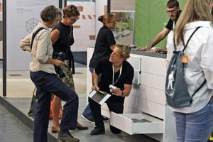 """Produktentwickler Andreas Brunkhorst zeigt den Besuchern am """"Labortisch"""" Entwürfe für zukünftige Produktentwicklungen."""