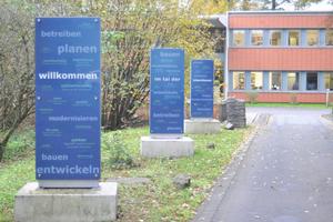 """Die drei Säulen """"Willkommen"""", """"Im Tal der"""" und """"Ideenbauer"""" empfangen die Besucher und Kunden."""