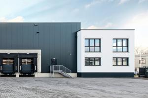 Das Bürogebäude bildet mit seinem weißen Außenputz einen starken Kontrast zum dunklen Hallenbau.