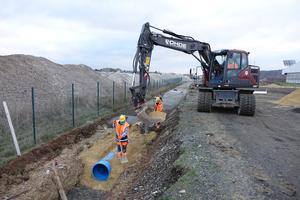 rechts: Der Rohrgraben wird mit auf die Baustelle geliefertem Ersatzmaterial verfüllt.