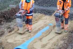 links: Mitarbeiter der Heinrich Rohde Tief- und Straßenbau verdichten den Rohrgraben fachgerecht.