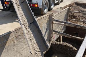 Der Flüssigboden wird in Transportmischern auf der Baustelle angeliefert und über eine Rutsche in den Rohrgraben eingefüllt.