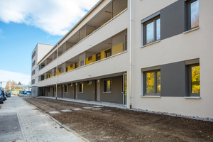 Rechts an den Kopfbau ist ein massiver Riegelbau angeschlossen: Dieser beinhaltet Ein- und Zweizimmerwohnungen, die über farblich gestaltete Laubengänge zugänglich sind.