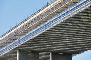 Die Lösung war ein Hängegerüst aus dem neuen Aluminium-Träger Flexbeam. Durch die hohe Tragfähigkeit des Ausbauteils konnten die Abhängepunkte an der Brücke um rund 60 Prozent reduziert werden.