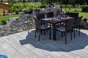 Die Terrasse wurde mit Stratos-Platten in Titangrau befes- tigt. Diese harmonieren mit der Mauer Vermont Kompakt in NeroBianco.