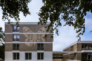 In dem Neubau sind verklinkerte Flächen in breite Streifen aus hellem Beton gefasst. Als besonderer Hingucker wurden Fassaden-ornamente in Form von gemauerten Schmetterlingen eingearbeitet.