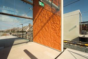 Die Oberfläche der Sichtbetonportale weisen das Relief eines stilisierten Fischschwarms auf.