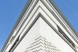 Auf dem massiven Klinkersockel mit erhöhtem Erdgeschoss setzen drei Obergeschosse in monolithischer Ziegelbauweise mit großen Verglasungen und unterschiedlichen Putzstrukturen an.