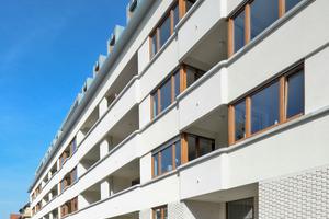 Der straßenseitige Teil des Gebäudes ist aus statischen Gründen mit dem dämmstoffverfüllten Poroton-Ziegel S9-MW in der Stärke 36,5 Zentimeter errichtet, im Bereich der Fensterbänder in der Stärke 30 Zentimeter. Die so entstandenen Rücksprünge rhythmisieren die Fassade horizontal, die Auskragungen an den Loggien vertikal.