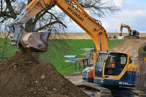R235LCR-9 und HX300 im Dauereinsatz in Dinkelsbühl-Sinbronn: Im Vordergrund wird Aushub gesiebt und für den Wiedereinbau vorbereitet. Der HX im Hintergrund erstellt einen neuen Hausanschluss.