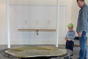 Quellschale aus Bronze im Inhalatorium. Das Heilwasser tritt langsam, von oben effektvoll beleuchtet, zu Tage.