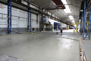 Aufbringen von Neodur HE 65: Über einen Mörtelschlauch wird das Material auf die Fläche transportiert. Die Flächen werden anschließend mit Tellerglättmaschinen abgerieben.
