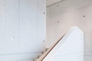 Im Treppenhaus bilden die Befestigungspunkte und das Fugenbild der einzelnen Betonabschnitte einen dezenten Hintergrund.