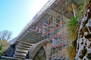 Für eine Brücken-sanierung konnte mit dem Allround-Gerüst in Verbindung mit dem hochtragfähigen Ergänzungsbauteil Flexbeam eine doppelstöckige Hängegerüstlösung inklusive Absturzsicherung für die Arbeiten auf der Brücke sowie Standgerüste im Bereich der Widerlagerrealisiert werden – aus Serienbauteilen.
