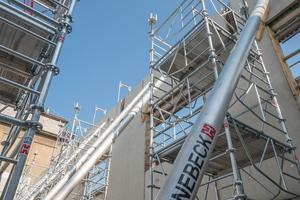10 m hohe ST-60-Stütztürme tragen die Schalung der mächtigen Ortbetonbinder und dienen als Arbeitsebene für die Schalung der Deckenfelder dazwischen.
