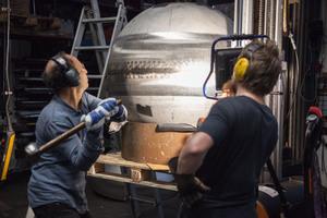 Herstellen der Kugeldüsen im Metallatelier. Vor dem Rundschleifen erfolgt noch manuelles Feinjustieren der Kugelform mit dem 3-kg-Hammer.