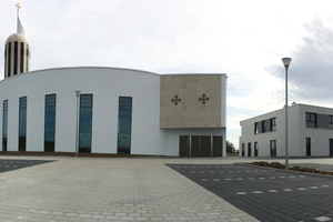 Der Parkplatz strukturiert das Gelände vor der Kirche.