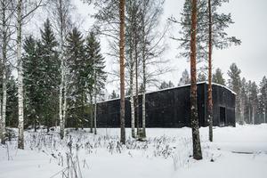 Die Wände aus schwarz pigmentiertem Beton erscheinen auf den ersten Blick wie alte, verkohlte Holzbohlen.