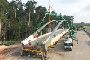 Die Fahrbahn wurde auf dem Tragwerk der Brücke betoniert und später mittels SPMTs auf den Widerlagern aufgesetzt.