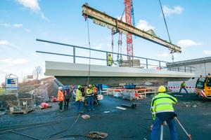 Einbau des Brückenüberbau-Randfertigteils mit Hybridkappe als Randabschlusselement sowie integriertem Geländer.