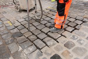 Für die Sanierung des Kopfsteinpflasters wird zunächst mit einem Hochdruckreiniger das Altmaterial aus den Fugen entfernt. Weitläufige und langwierige Sperrungen der Straße sind nicht nötig.