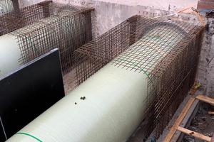 Eine Betonummantelung dient zur Auftriebssicherung der Flowtite Kanalrohre. Der bewehrte Bereich schafft außerdem eine kraftschlüssige Verbindung zur Stahlbetonsohlplatte.