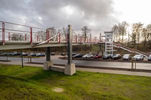 Über eine Treppe und einen Aufzug ist die Brücke an den darunterliegenden Bahnhof mit P+R-Parkplatz angebunden.<br /><br />