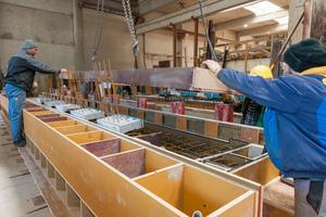 Um den Beton über die Anschlussöffnung einzufüllen, drehten die Arbeiter im Fertigteilwerk die Schalungen, in denen sich auch die tragenden Wärmedämmelemente befinden, um 90 Grad.