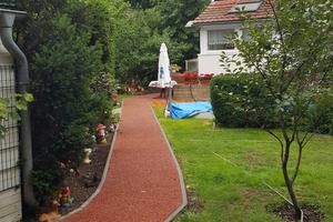 Ein privater Bauherr aus Königs Wusterhausen ließ zwei Parkplatzflächen und einen Weg mit rot eingefärbtem Dränbeton ausführen.