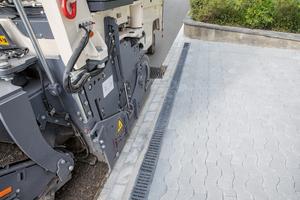 Das eingeschwenkte rechte Hinterrad erlaubt präzises Fräsen entlang von Hindernissen wie Bordsteinen oder Mauern.