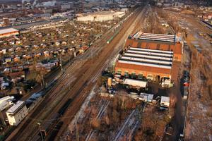 """Lokhalle Freiburg vor dem Umbau. Das denkmalgeschützte Gebäudeensemble beherbergt heute den """"Kreativpark"""" mit attraktiven Büroflächen, dazu kommen Ende 2021 eine Gastronomie und ein Softwareunternehmen. Das Regenwasser von Dach- und Hofflächen wird zu 100 % unterirdisch behandelt und versickert."""