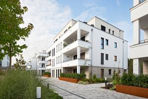 Zwischen den Mehrfamilienhäusern aus Ziegelmauerwerk befindet sich eine Grünfläche. Während die unteren Etagen loggienartige Balkone erhalten, verfügt das Penthaus über eine Dachterrasse.