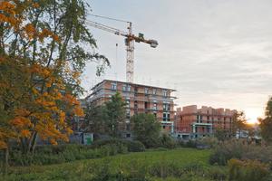 Mit begrünten Flachdächern und einer verkehrsberuhigten Grünfläche im Zentrum gliedern sich die 13 Gebäude gut an.