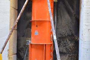 Die Stahlschalungselemente sind inklusive der unteren Sonderkonstruktion exakt auf die lichte Höhe von 3,66 m zusammengestellt. Am Sonderbauteil ist der Druckschlauchanschluss zu sehen. Nach dem Aushärten der Betonsäule werden die vorhandenen Betonkonstruktionen links und rechts der Stütze weiter abgebrochen.