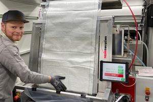 Ein Fach über dem Vakuum-Imprägnierer hilft bei der Führung längerer Glasfasermatten. Das Harz liefert die Dosiertechnik direkt hinter dem Vakuum-Imprägnierer – luftfrei und perfekt gemischt.