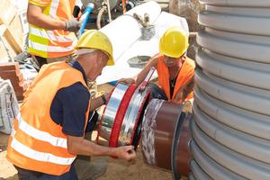 Die Tiefbauer montieren die VPC-Rohrkupplung am Eiprofilspitz-ende des Schachtes DN 1000.
