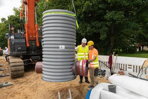 Der vorbereitete Schacht DN 1000 wird in die Baugrube eingehoben.