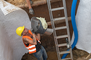 Der BI-Adapter Eiprofil wird zum Einbau in die Bestandsleitung in die Baugrube gereicht.
