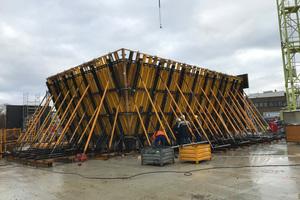 Die 60 Zentimeter starken schrägen Leichtbetonwände des Erdgeschosses, die innen glatt, nach außen aber abgestuft sind und hier die für das Gebäude charakteristische Holzstruktur aufweisen, wurden mit Sonderschalungselementen von Ulma erstellt.
