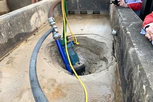 Eine Tsurumi-Pumpe mit Spülkranz frisst sich durch dickstes Sediment und leert das verschlammte Becken.<br />